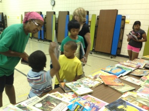 A site director helping the children pick out books